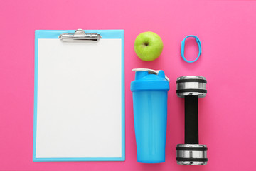 Clipboard with blank paper for exercise plan and gym stuff on color background. Flat lay composition