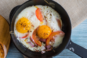 Fried eggs with tomatoes and onions in a cast iron pan on a rustic wooden background