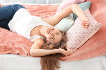 Portrait of beautiful smiling woman on bed at home