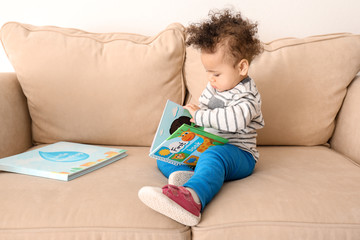 Cute little child with colorful book on sofa at home
