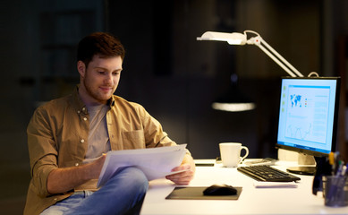 businessman with papers working at night office
