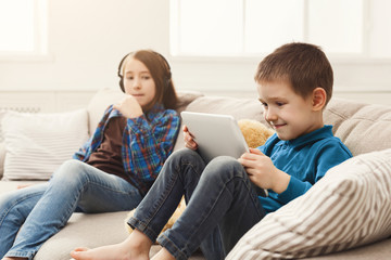 Two kids with gadgets on couch at home