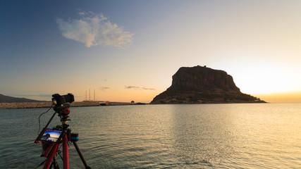 Camera on tripod and Monemvasia island sunrise