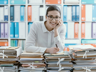 Smiling office clerk and piles of paperwork