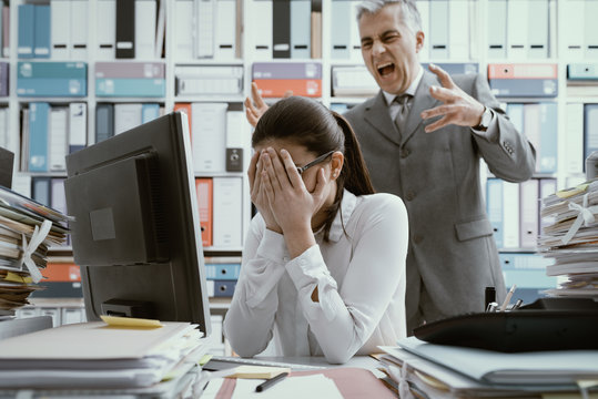 Angry boss yelling at his young employee