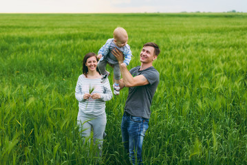 Joyful man, woman walk on green field background, rest, have fun, play, toss up little cute child baby boy. Mother, father, little kid son. Family day 15 of may, love, parents, children concept.