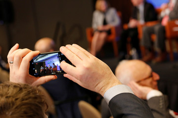 "A man in the audience takes a cell phone picture during a Reuters Newsmakers panel titled ""Banking Culture: Still Room for Improvement?"" in the borough of Manhattan"