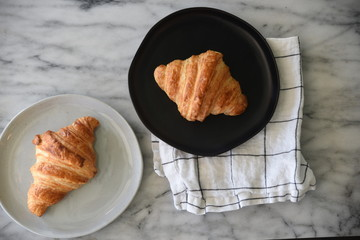 Two croissants on plates, overhead view