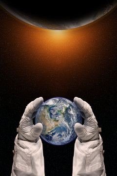 Earth in the hands of astronaut. Earth Day concept. Elements of this image furnished by NASA.
