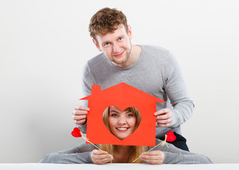 Positive couple with heart house.