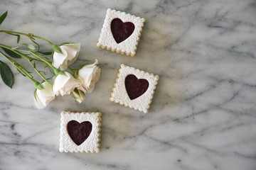 Cookies with heart shaped decoration, with flowers, overhead view