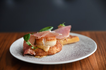 Scallop with ham on white plate, close-up