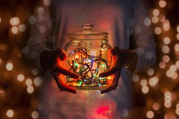 Girl hands holding mason jar with fairy lights