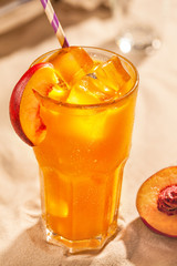 Summer cold drinks: peach sangria with ice cubes in glass on sand background