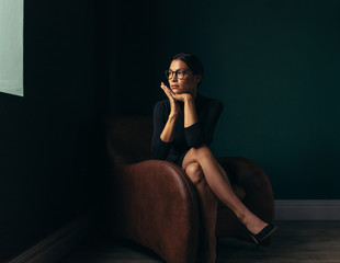 Pensive young woman sitting on chaise longue