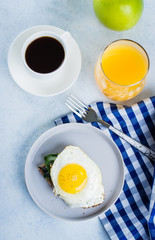 Rye bread toasts with fried spinach and egg with cup of coffee and orange juice on blue table background. Healthy Breakfast Food Concept. Flat Lay, top view