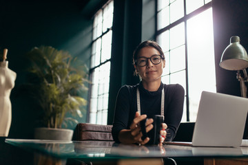 Female designer sitting at her desk with coffee