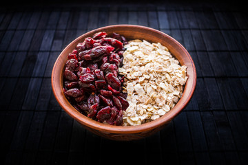 Raw oatmeal with dried cranberries in a round clay bowl on a dark wooden background. Healthy fitness vegetarian breakfast granola meal with cranberries. Selective focus