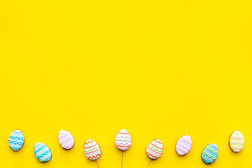 Easter gingerbread and cookies in shape of Easter eggs. Yellow background top view copy space