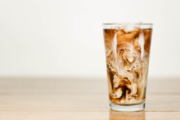 Iced coffee on a wood table with cream being poured into it showing the refreshing drink with a clean background