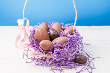 Photo of chicken , chocolate eggs, purple decorative paper in basket