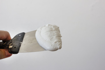 Spatula with putty on white background