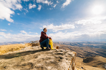 happy woman tourist sits on the background of mountains on a sunny day