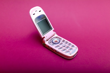 Cool and classic pink retro flip cell or mobile phone isolated against a red background
