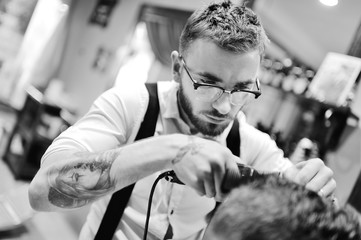 Stylish barber with a beard and with glasses cuts hair to the client on a background of barbershop