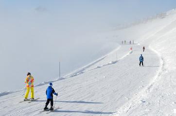 """Сочи, горнолыжный курорт Роза Хутор. Лыжники в яркой спортивной одежде спускаются с горнолыжной трассы """"Горицвет"""" в условиях ограниченной видимости"""