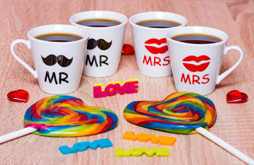 LGBT community concept. Four cups of coffee for friends, rainbow lollipops, love and hearts