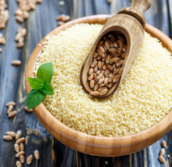 Scoop with wheat in a wooden bowl with couscous.