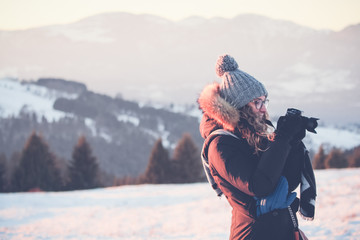 Blonde smiling girl on the snow, checking the picture just taken
