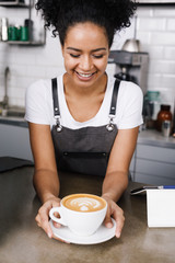Happy waitress looking at cup of coffee