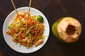 delicious divine asian pad thai with seafood lime and japanese stick with coconut beverage close up photo