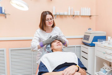 Woman doctor doing facial massage with electric gloves in cosmetology clinic