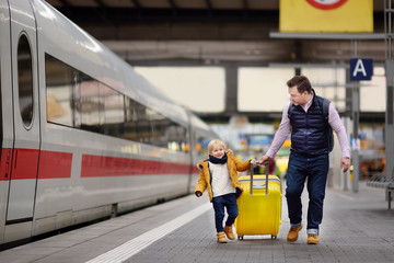 Cute little boy and his father waiting express train on railway station platform