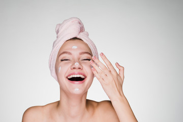 happy woman with a towel on her head puts on a face cream