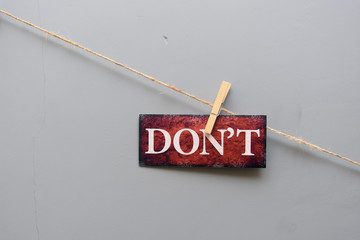 """Sign """"don't"""" clipped on a rope on background of a dark gray wall"""