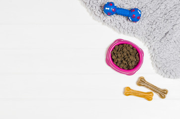 Dry dog pet food in bowl on white wooden background top view. Pet feeding concept backgrounds with copy space. Photograph taken from above.