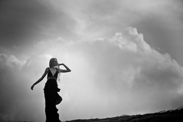 A young blonde girl walking in the long black dress in the desert