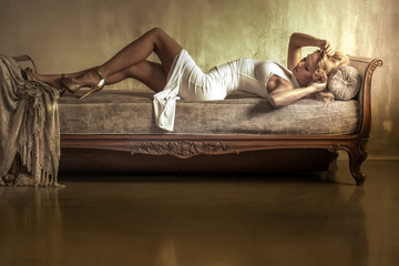 Portrait of a beautiful young woman laying on a antique Sofa at night.