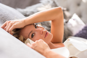 Portrait of a beautiful young woman laying on the bed.