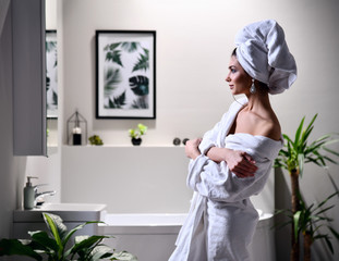 Young beautiful woman with white towel on head do makeup looking at the mirror wearing bathrobe