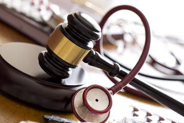 Medicine law concept. Judges gavel with  stethoscope  and pills close up