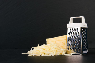 Grater and cheese on dark slate background