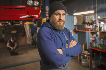 A bearded car mechanic works in the garage