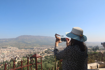 Female traveller make a panoramic photo of the old city