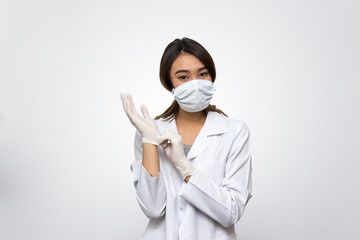 Portrait of a young friendly doctor in medical mask taking off sterile gloves and looking at camera isolated on white background. Medicine and healthcare concept