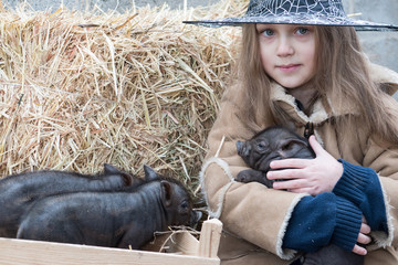 A happy girl in a witch's masked hat plays with newly born pigs. Winter farm yard. The concept of childhood in the village. Creative leisure with kids on swine farm